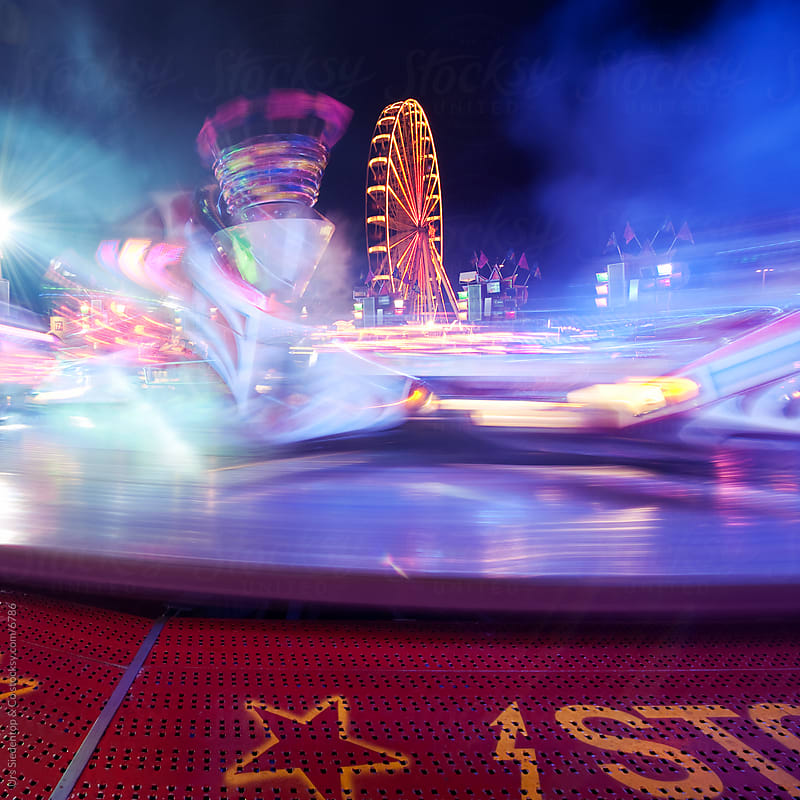 Illuminated motion blured carnival ride at night by Urs Siedentop & Co for Stocksy United