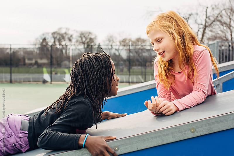 African American and Caucasian friends chatting on a skateboard ramp by Gabriel (Gabi) Bucataru for Stocksy United