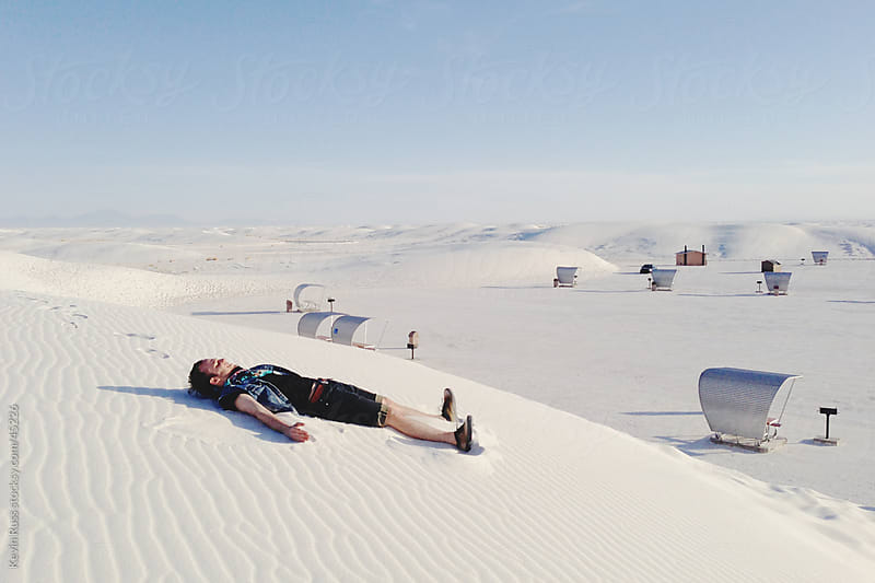 Man Makes Sand Angel on White Sand by Kevin Russ for Stocksy United
