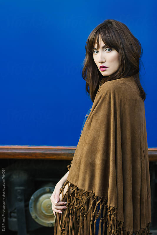 Portrait of a female model in poncho by Evil Pixels  Photography for Stocksy United
