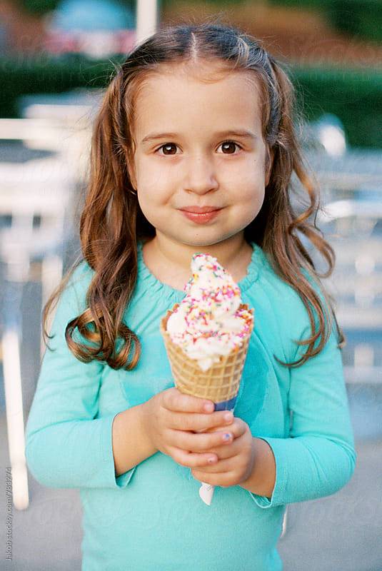 Cute young girl holding a large ice cream by Jakob for Stocksy United