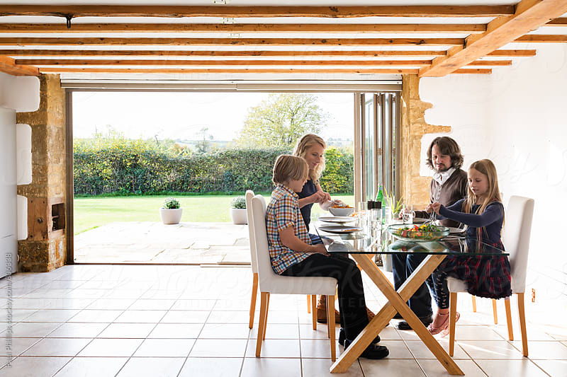 Spacious dining area in a modern timber framed house with a family having lunch. by Paul Phillips for Stocksy United