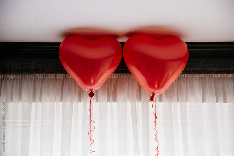 2 red heart balloons for Valentine's day by Beatrix Boros for Stocksy United