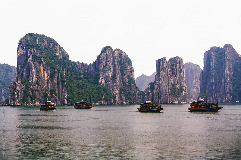 Ships navigating with rock formations on the sea in Halong Bay, Vietnam by Alejandro Moreno de Carlos for Stocksy United