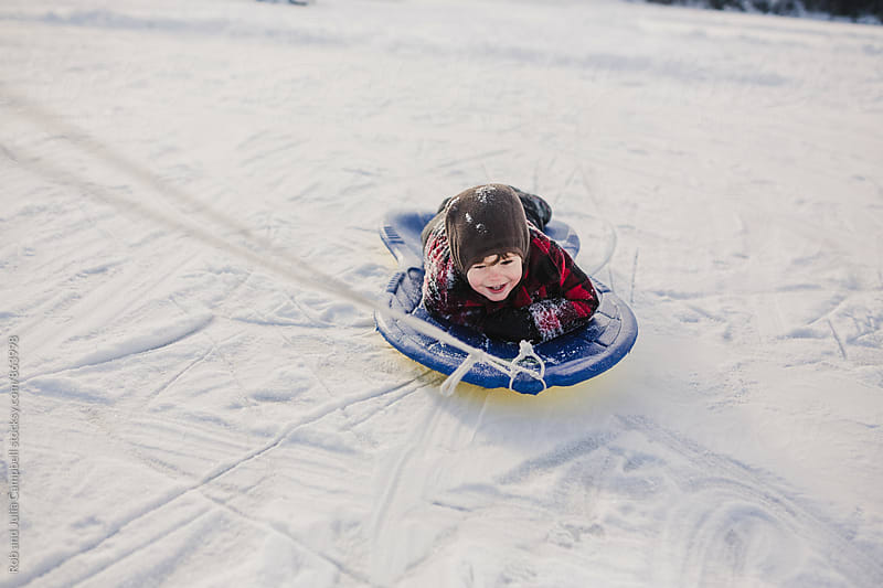 Happy kid playing in the snow - getting dragged on a sled by Rob and Julia Campbell for Stocksy United