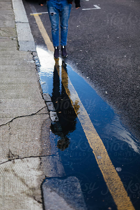 Young Woman Standing Close to a Puddle on the Street by HEX. for Stocksy United