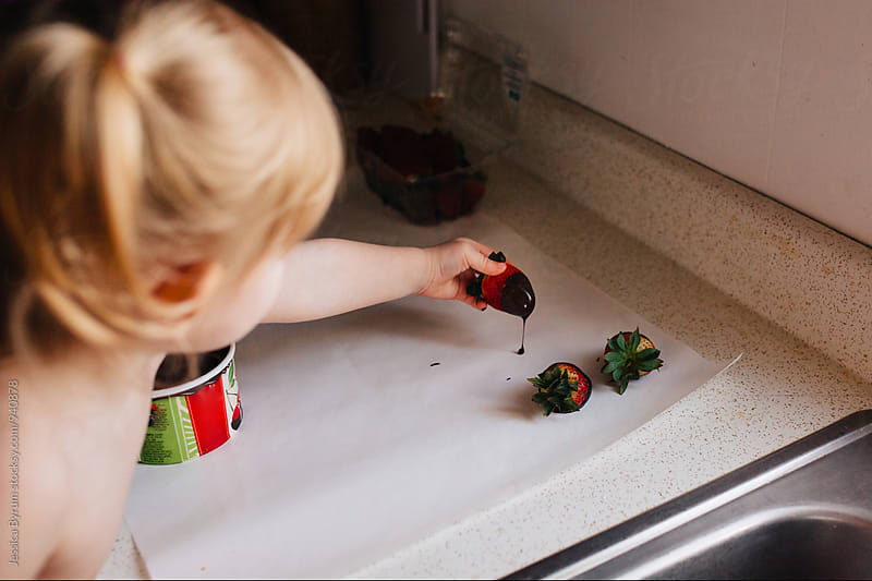 Young child making chocolate covered strawberries by Jessica Byrum for Stocksy United