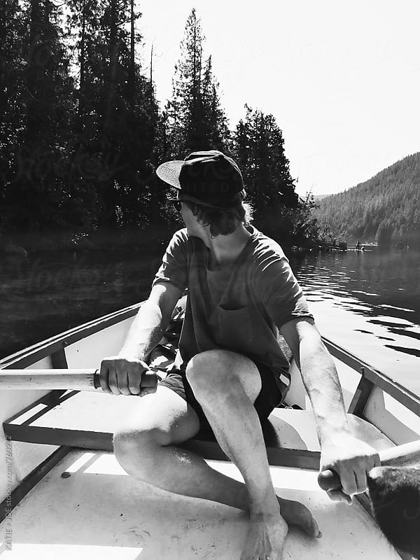 Black and white photo of a man in a rowboat by KATIE + JOE for Stocksy United