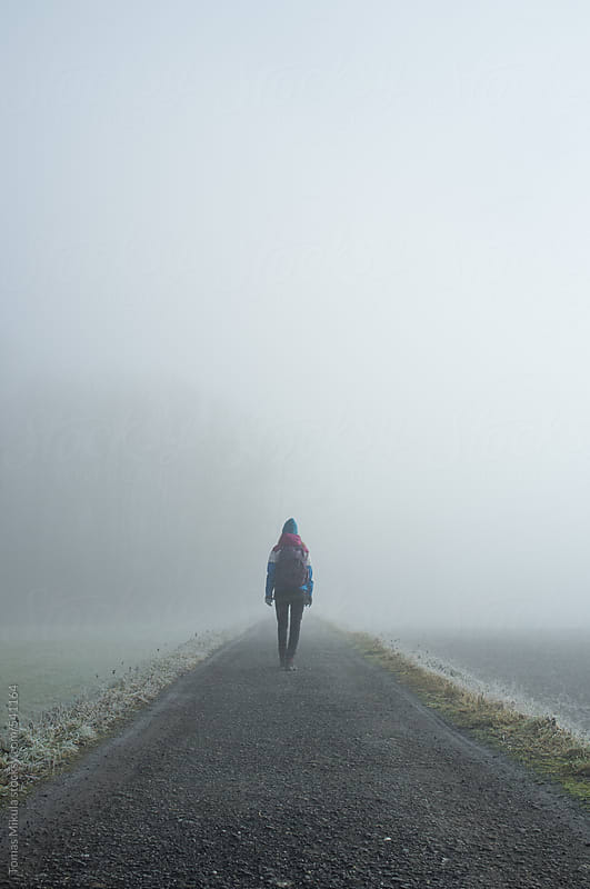 Girl with bag standing on the road in the foggy morning by Tomas Mikula for Stocksy United