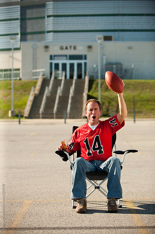 Tailgating: Fan Sits Alone in Lot Waiting for Game by Sean Locke for Stocksy United