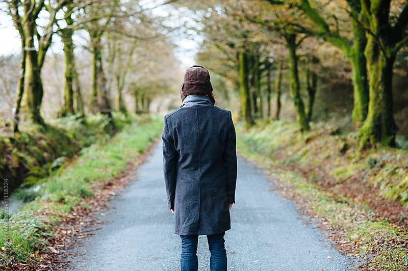 Man standing on a country road in autumn by Suzi Marshall for Stocksy United