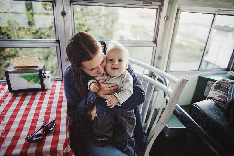 Young mom snuggling baby boy inside at table by Rob and Julia Campbell for Stocksy United