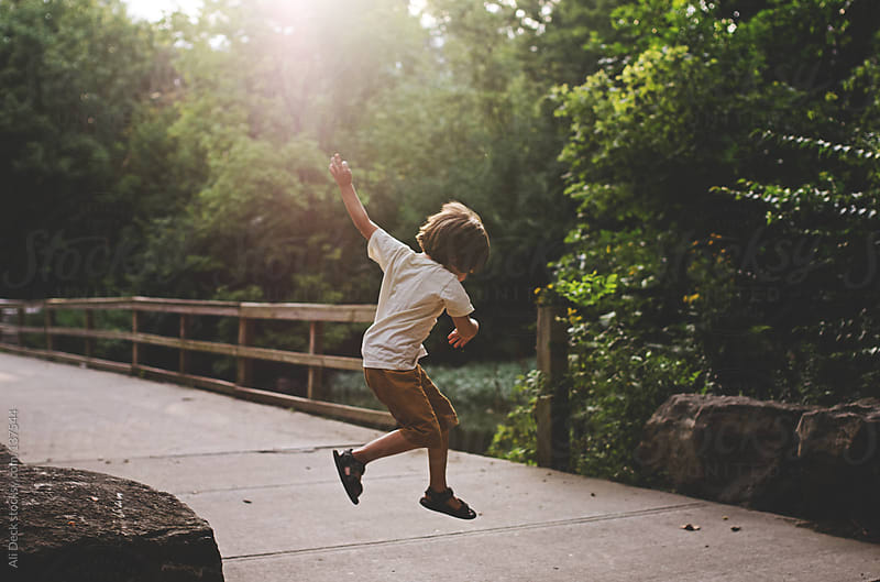 A boy jumping off a boulder at sunset. by Ali Deck for Stocksy United