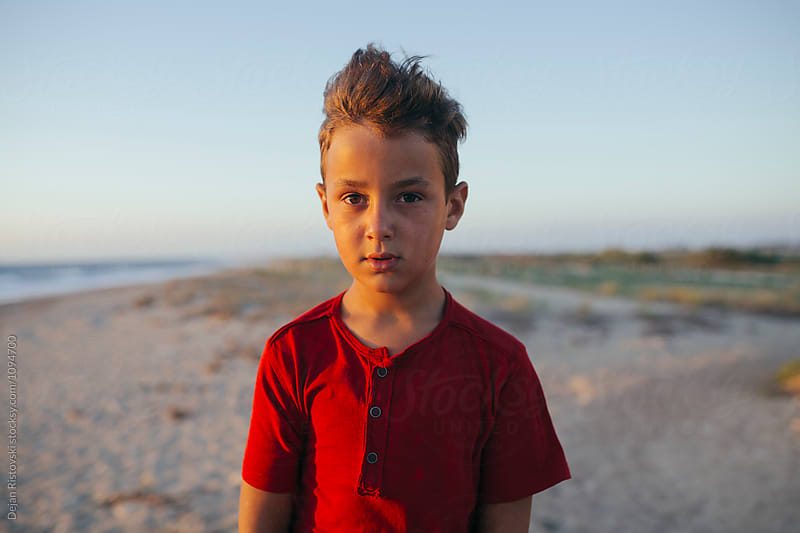 Boy standing on the beach and looking at camera, by Dejan Ristovski for Stocksy United