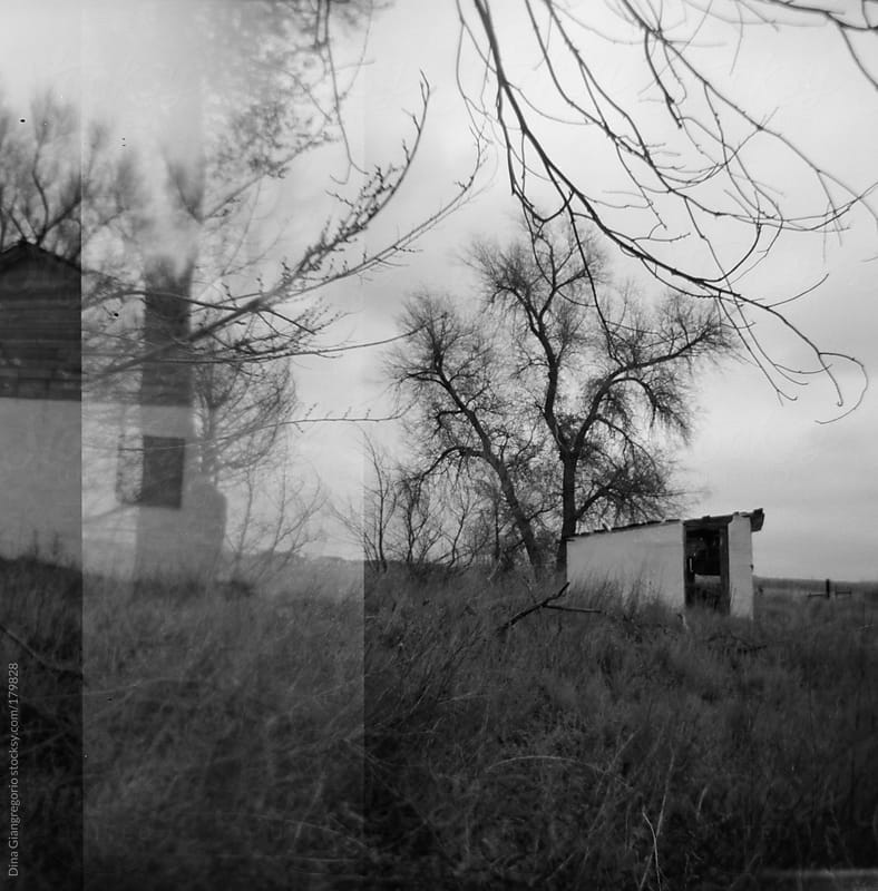 Multiple exposures in film showing two different deserted  houses by Dina Giangregorio for Stocksy United