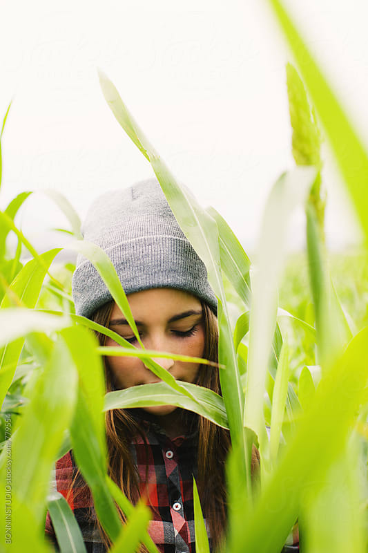 Teen girl hidden between corn field. by BONNINSTUDIO for Stocksy United