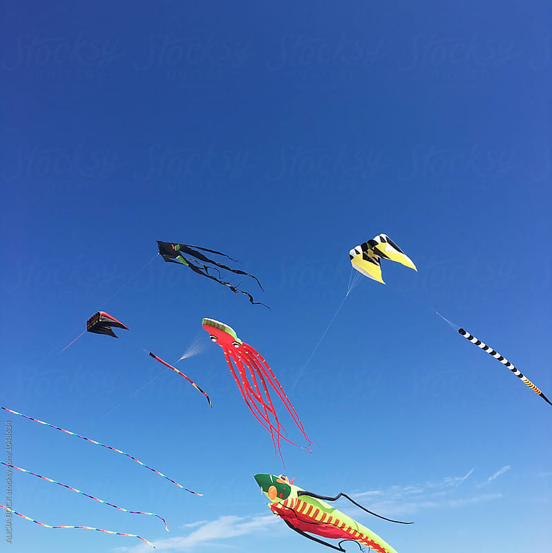 Kites Flying Against A Clear Blue Sky On A Summer Day by ALICIA BOCK for Stocksy United