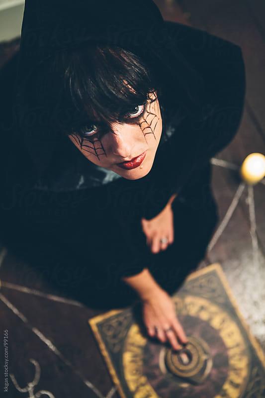 Woman sitting inside a pentagram using a Ouija board. by kkgas for Stocksy United