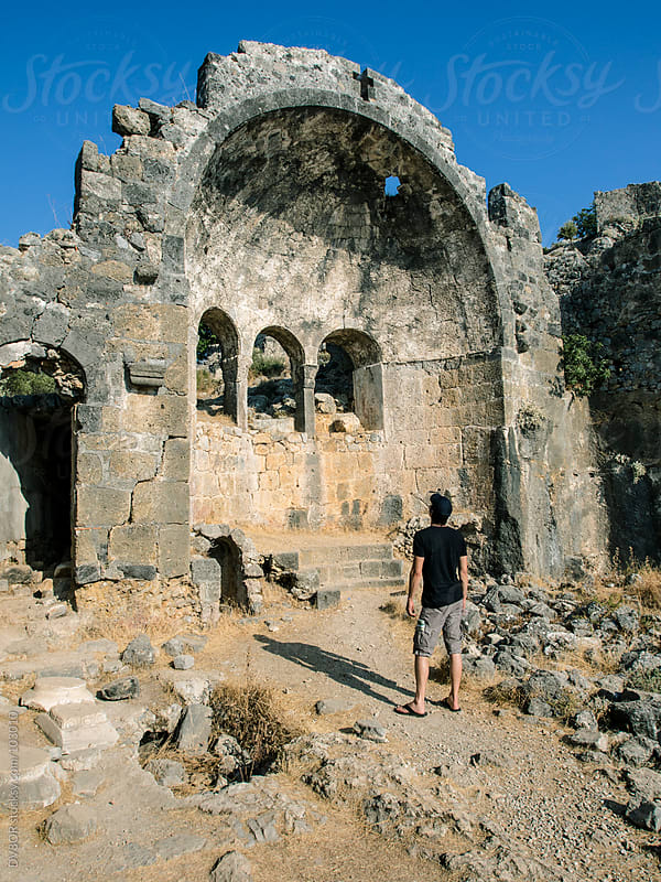 Man looking at a ruin of a church on Gemiler Island, Fethiye, Turkey by DV8OR for Stocksy United
