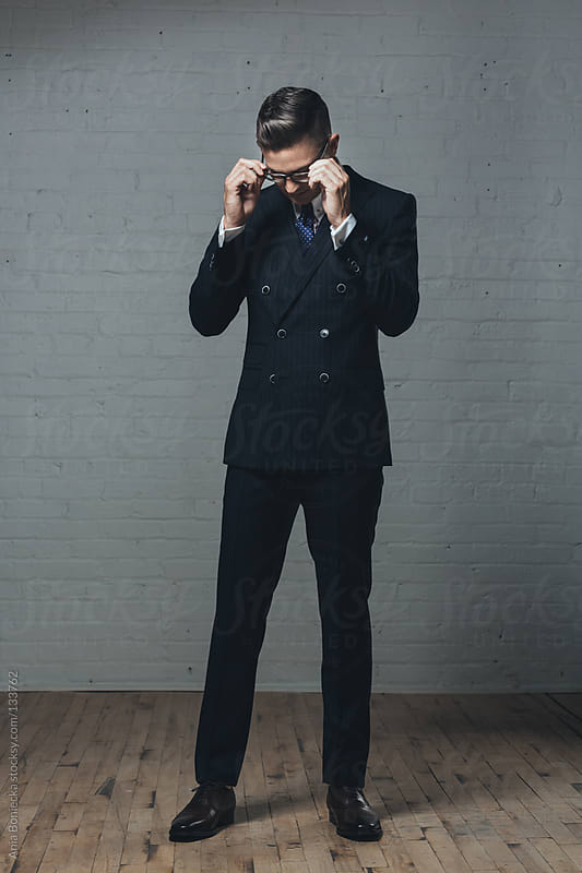 A man in a double breasted suit adjusting his eye glasses by Ania Boniecka for Stocksy United