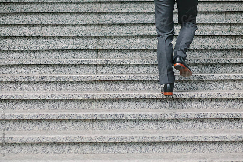The back of the legs of a businessman running up the concrete stairs by Ivo de Bruijn for Stocksy United