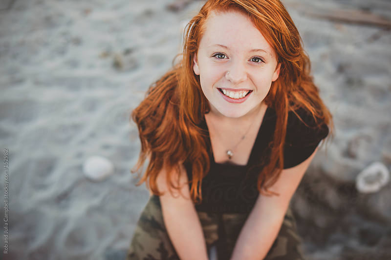 Happy portrait of redhead teenage girl sitting at the beach by Rob and Julia Campbell for Stocksy United