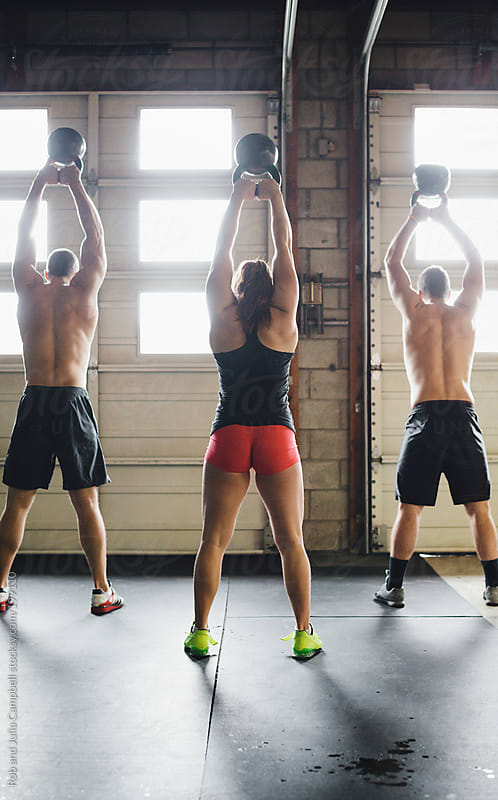 Group of workout friends lifting kettlebells together by Rob and Julia Campbell for Stocksy United