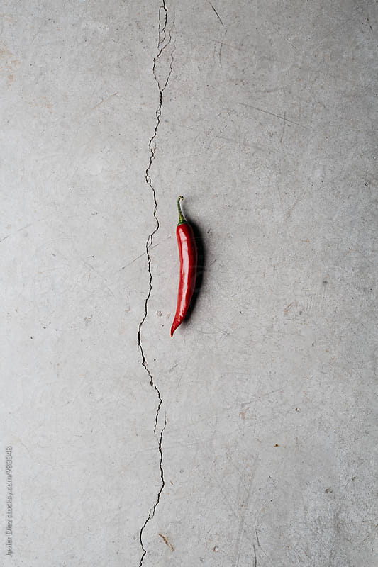 Close-up of chilli on grey background by Javier Díez for Stocksy United