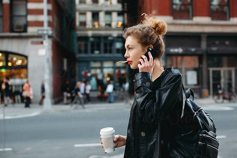 Business woman walking down the street holding up her cell phone and her coffee mug by michela ravasio for Stocksy United