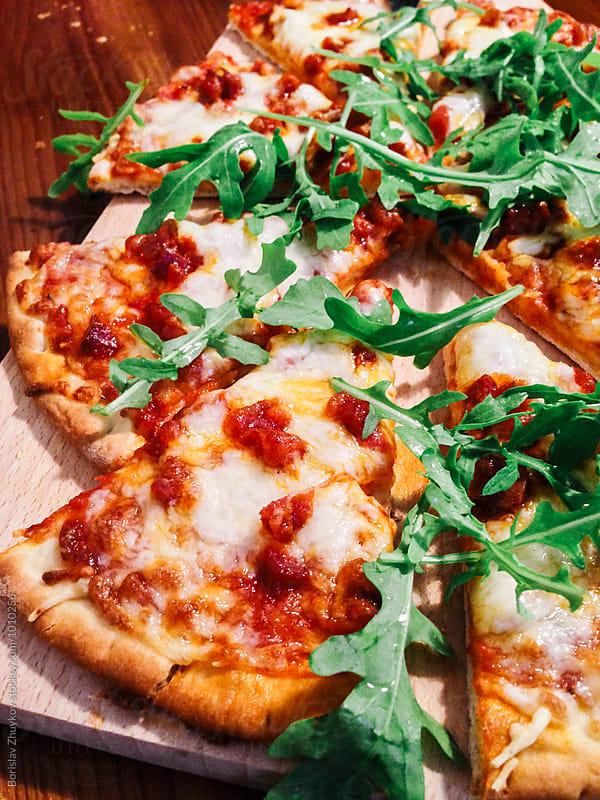 Sliced pizza with chorizo, parmesan and arugula by Borislav Zhuykov for Stocksy United