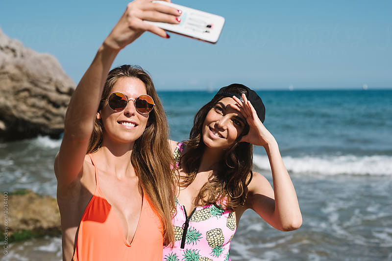 Two girls taking a self portrait at the beach by Simone Becchetti for Stocksy United