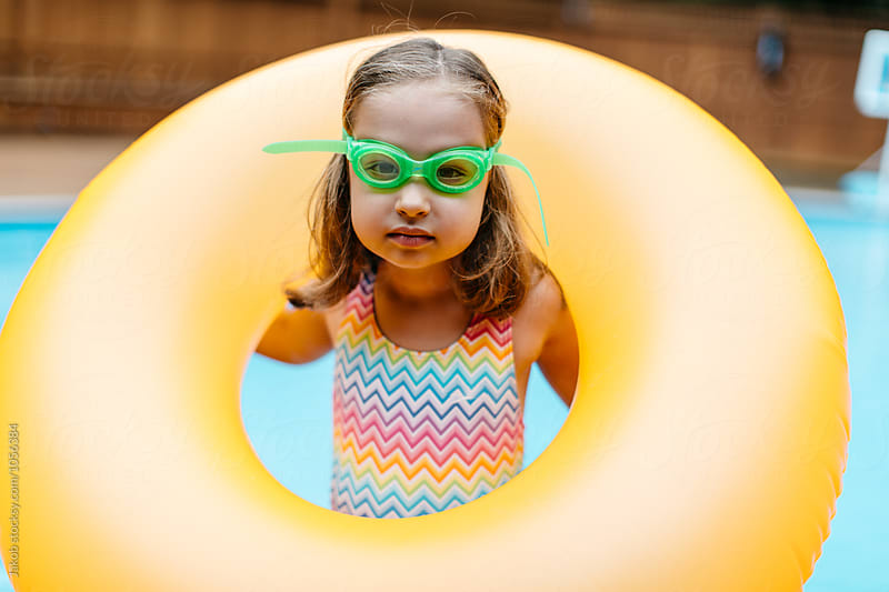 Cute young girl playing with her inner tube by a pool by Jakob for Stocksy United