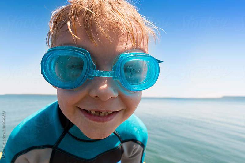 Boy Wearing Goggles at Summer Lake on Water Trampoline At Cottage by JP Danko for Stocksy United