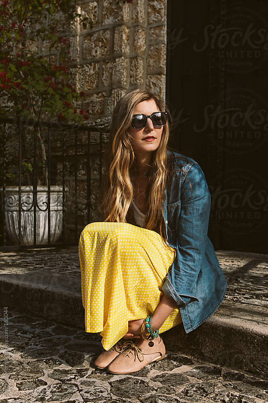 Woman in denim shirt and yellow skirt by Stephen Morris for Stocksy United