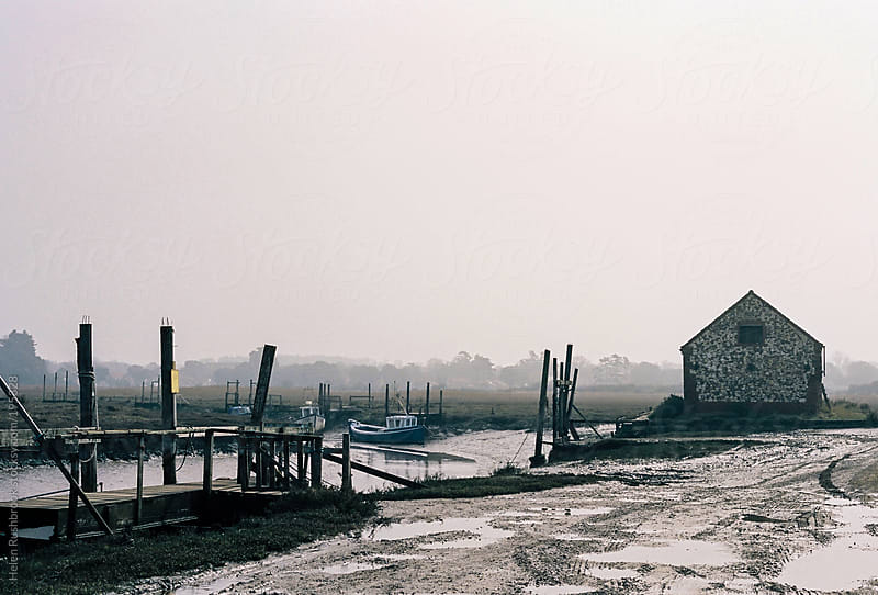 A foggy harbour at low tide. by Helen Rushbrook for Stocksy United