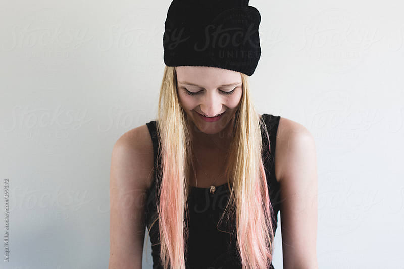 Laughing teen girl with long blonde and pink hair is wearing a black beanie by Jacqui Miller for Stocksy United