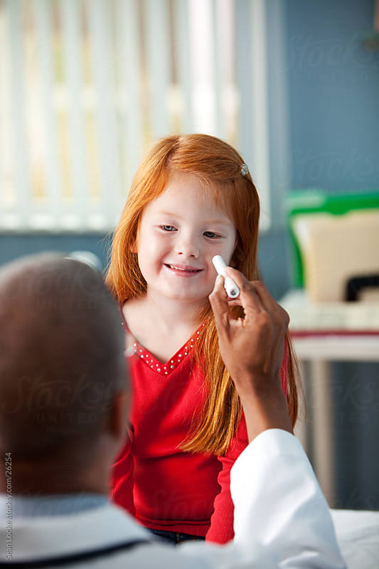 Exam Room: Girl Smiles at Doctor During Check Up by Sean Locke for Stocksy United
