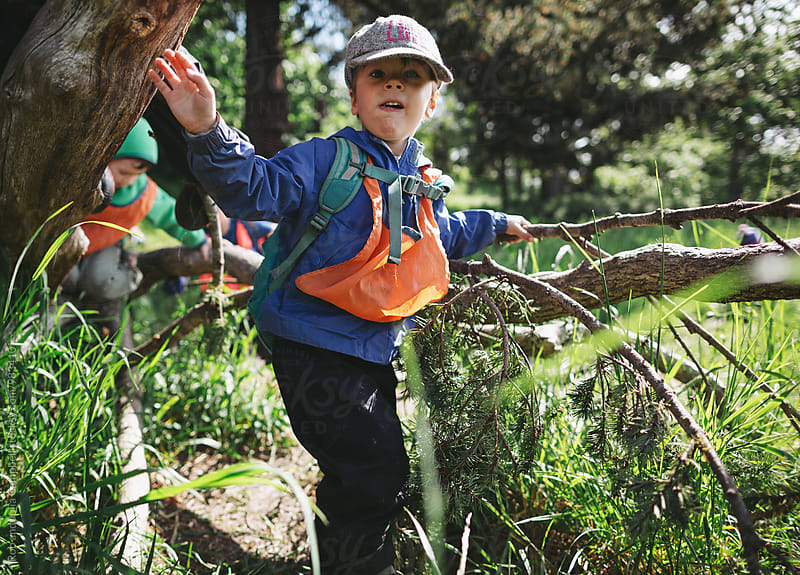 Young caucasian boy climbing fallen tree at nature preschool by Rob and Julia Campbell for Stocksy United