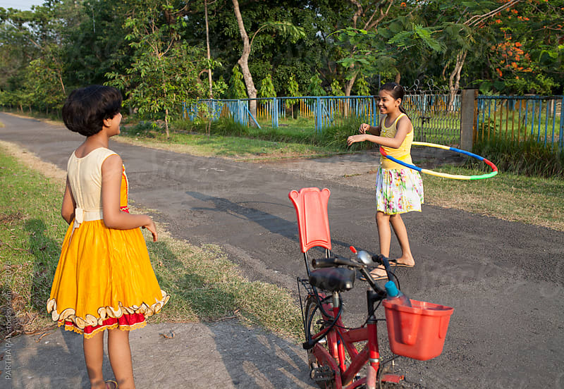 Two bengali girl playing and making fun with  hula hoop by PARTHA PAL for Stocksy United