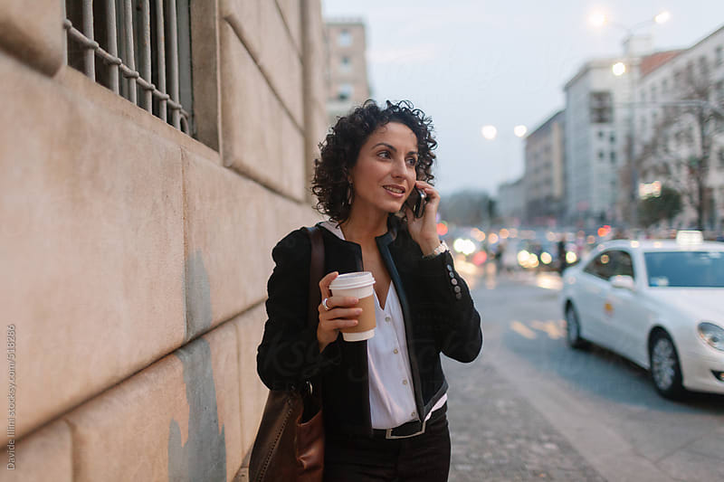 Young woman on the phone in the business district by Davide Illini for Stocksy United
