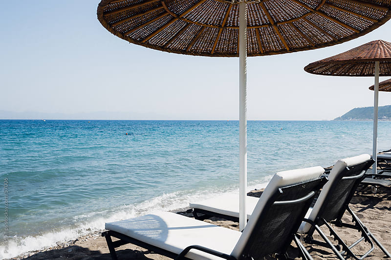 Beach parasols, sunbeds and sea by Paul Phillips for Stocksy United