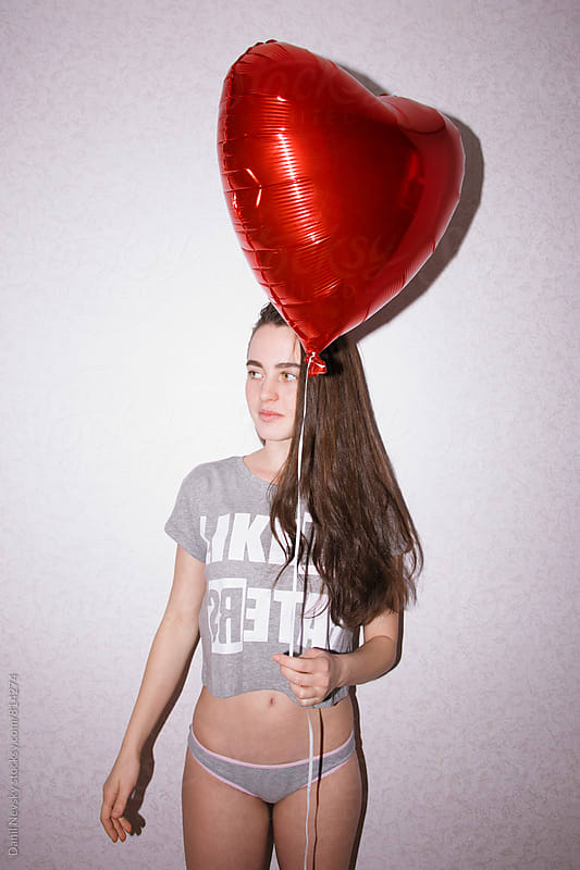 Portrait of young woman holding red balloon by T-REX & Flower for Stocksy United