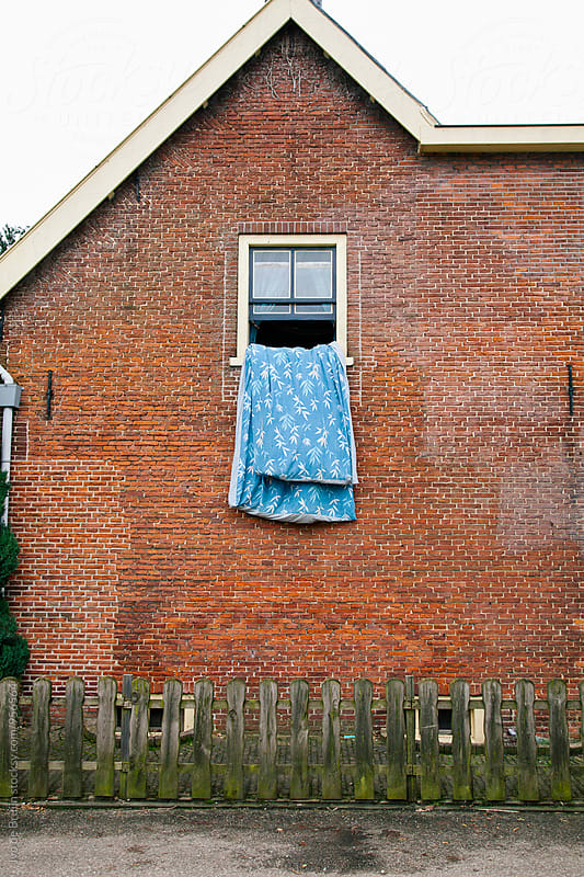 Blanket hanging out of a brick house with the window open by Ivo de Bruijn for Stocksy United