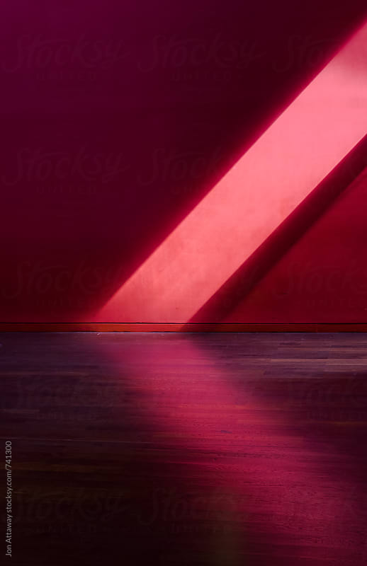 Ray of sunlight falling against a red wall by Jon Attaway for Stocksy United