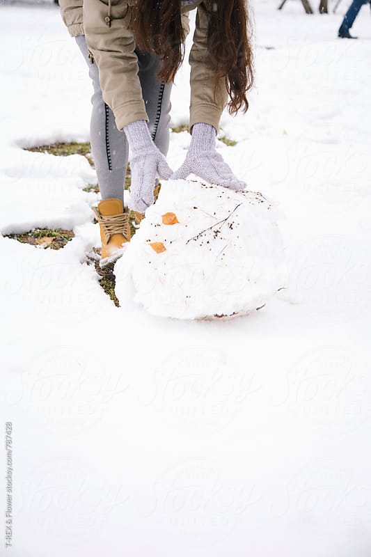 Woman rolling a snowball  by T-REX & Flower for Stocksy United