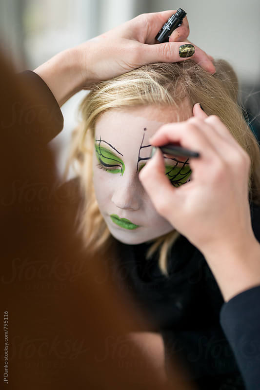 Mother Applying Face Paint Make Up for Little Girl Witch Halloween Costume by JP Danko for Stocksy United