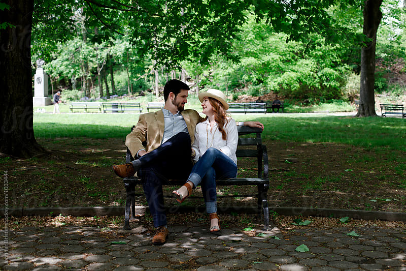 Couple in love sitting on bench in park  by Jennifer Brister for Stocksy United