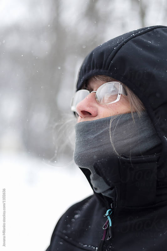 Portrait of a beautiful senior woman standing outside looking at the falling snow