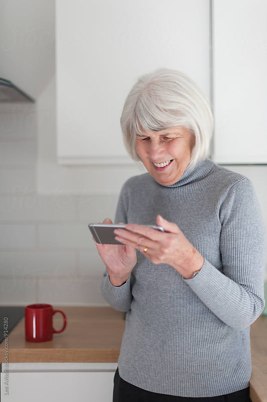 senior woman using a mobile device by Lee Avison for Stocksy United
