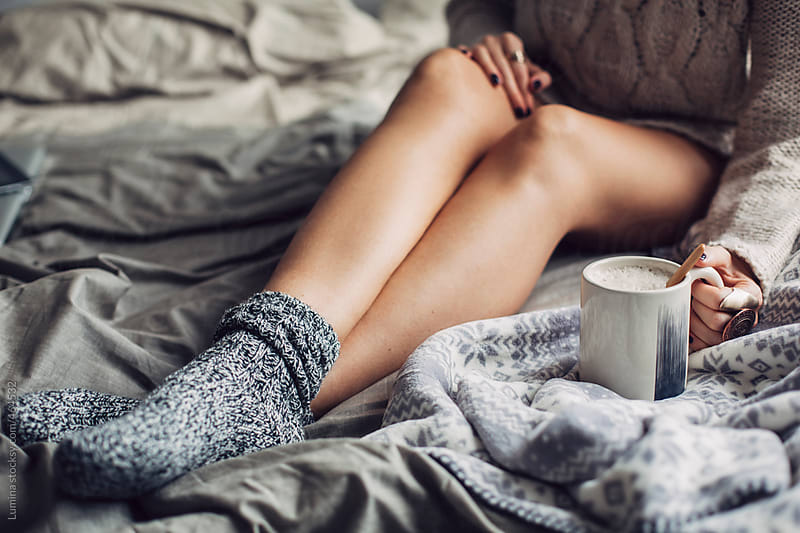 Woman In Woolen Socks Drinking Hot Coffee in Bed in the Morning by Lumina for Stocksy United